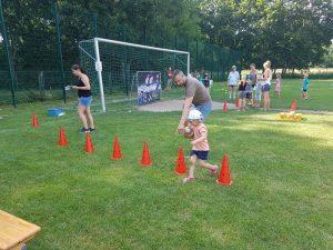 Kinder und Erwachsene spielen auf einem Rasen. Im Hintergrund ist ein Fußballtor zu sehen. Im Vordergrund sechs rote Hütchen.