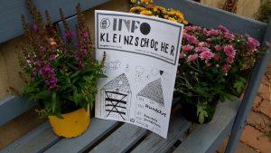 """Das Magazin """"Info Kleinzschocher"""" ist auf einer Bank zwischen Blumen zu sehen."""