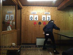 Es ist eine Tischtennisplatte im Kunstraum Praline zu sehen. Eine junge Frau spielt gegen einen Roboter. Der Spielstand hinten an der mit Holz vertäfelten Wand sagt: 4:3 für Human against Robot.